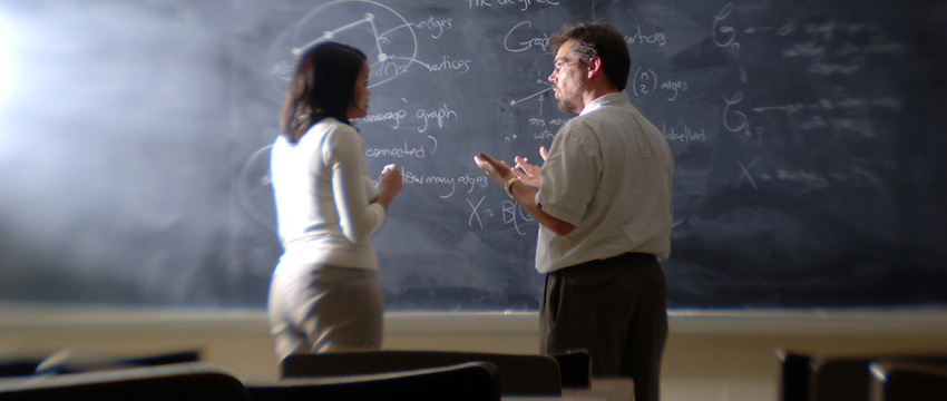 Instructor and student discuss in front of blackboard