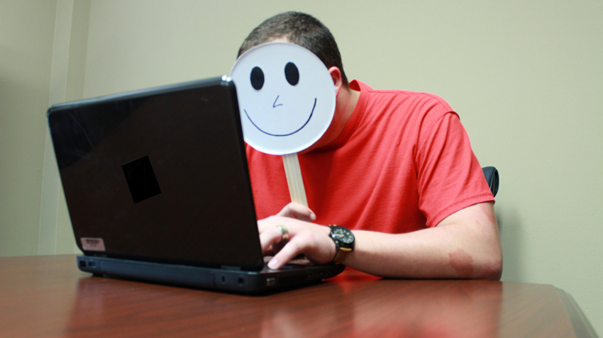 A masked man using a laptop